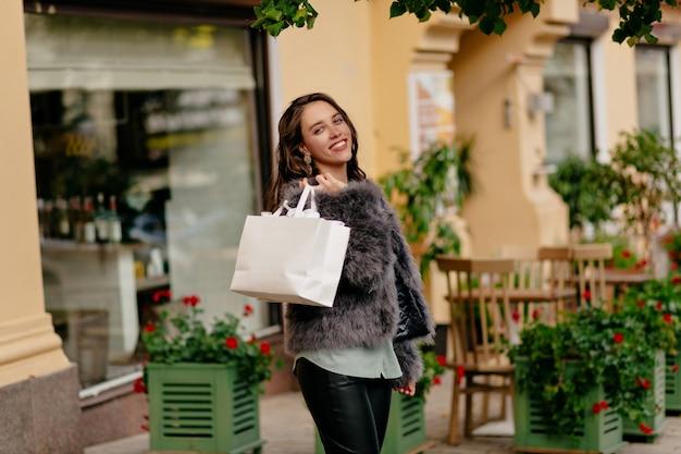 Poza portret stylowa nowoczesna dziewczyna ubrana w futro, chodzenie po ulicy z torbą po zakupach