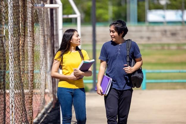 Poza szkołą szczęśliwa młoda para uczniów stoi wzdłuż płotu i studiuje książkę.