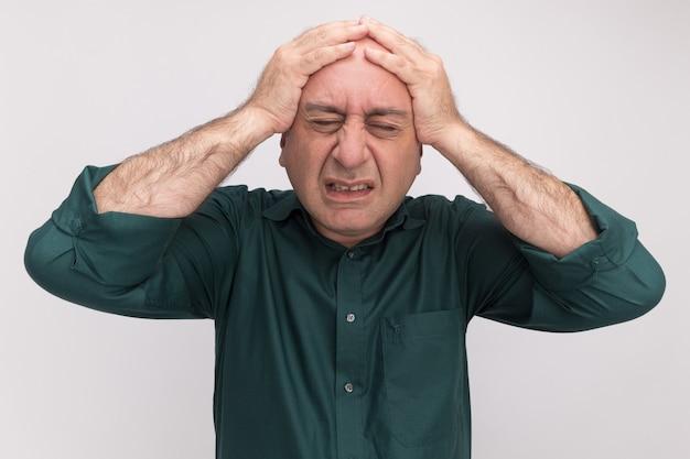 Pożałowany z zamkniętymi oczami mężczyzna w średnim wieku ubrany w zieloną koszulkę złapał za głowę odizolowaną na białej ścianie