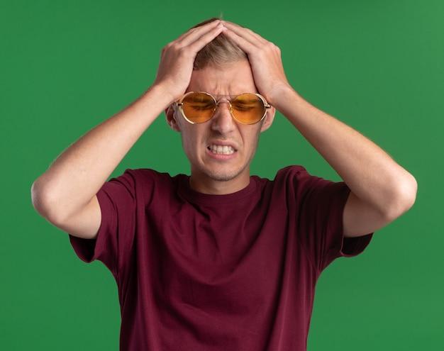 Pożałowany z zamkniętymi oczami młody przystojny facet w czerwonej koszuli i okularach złapał głowę odizolowaną na zielonej ścianie