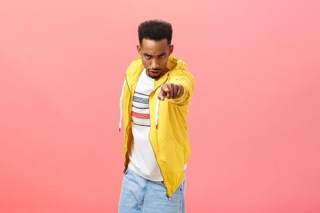 Pożałujesz tego. portret grożącego zły i wkurzony niebezpiecznego afroamerykańskiego młodego człowieka patrzącego spod czoła z pogardą i wściekłością wskazującego na kamerę obwiniającą kogoś o różową ścianę