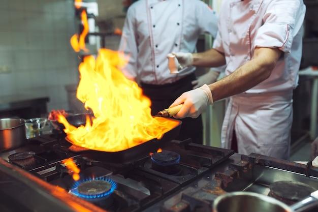 Pożar w kuchni. oparzenie gazem kuchennym gotuje się na żelaznej patelni, mieszając ogień bardzo gorący