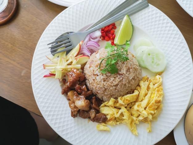 Pożarniczy ryż z wieprzowiną i podpalają jajko na drewno stole