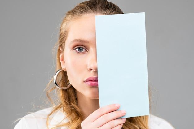 Pozbawiona emocji długowłosa kobieta o niebieskich oczach i różowych ustach trzymająca kawałek przezroczystego papieru