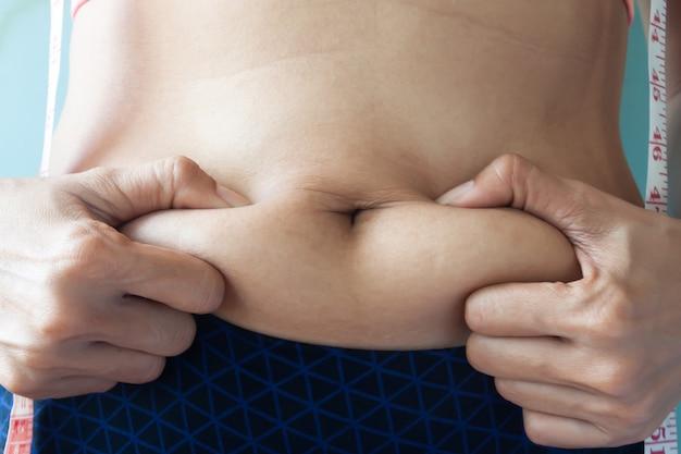 Pozbycie się tłuszczu z brzucha, diety, utraty wagi lub koncepcji wzmocnienia. kobieta ściska brzuch