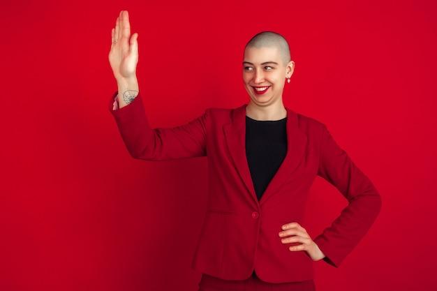 Pozdrawiam kogoś. portret młodej kobiety kaukaski łysy na białym tle na czerwonej ścianie. piękna modelka w kurtce. ludzkie emocje, wyraz twarzy, sprzedaż, koncepcja reklamy. zakręcony.