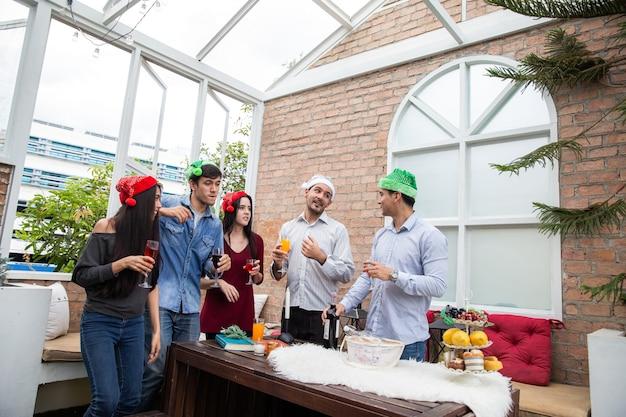 Pozdrawiam najlepszych przyjaciół wesołych młodych ludzi dopingujących kieliszkami szampana i wyglądających na szczęśliwych