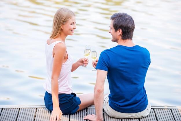 Pozdrawiam! piękna młoda kochająca para siedzi razem na nabrzeżu i pije szampana