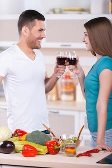 Pozdrawiam! piękna młoda para trzymająca kieliszki z czerwonym winem i patrząca na siebie stojąc w kuchni