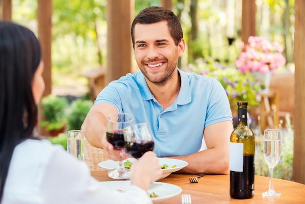Pozdrawiamy nas! szczęśliwa młoda kochająca para opiekająca czerwone wino i uśmiechnięta podczas wspólnego relaksu w restauracji na świeżym powietrzu