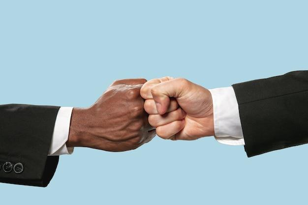 Pozdrowienia przyjaciół podpisują lub nie zgadzają się. dwóch męskich rąk konkurencja w siłowaniu się na rękę na białym tle na niebieskim tle.