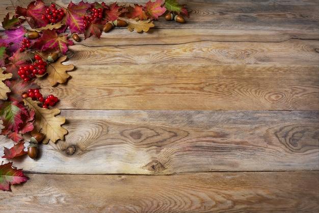 Pozdrowienie dziękczynienia z jagodami, żołądź, jesienne liście na drewnianym tle. święto dziękczynienia tło z symbolami sezonowymi. skopiuj miejsce.