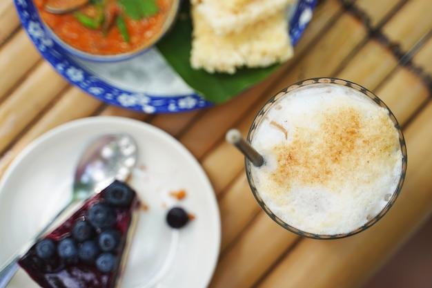Pozioma scena kulinarna mrożonej tajskiej pomarańczowej herbaty mlecznej ze świeżym mlekiem i świeżymi deserami