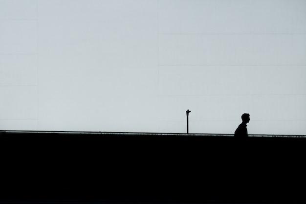 Pozioma sylwetka samotnego mężczyzny pod czystym niebem