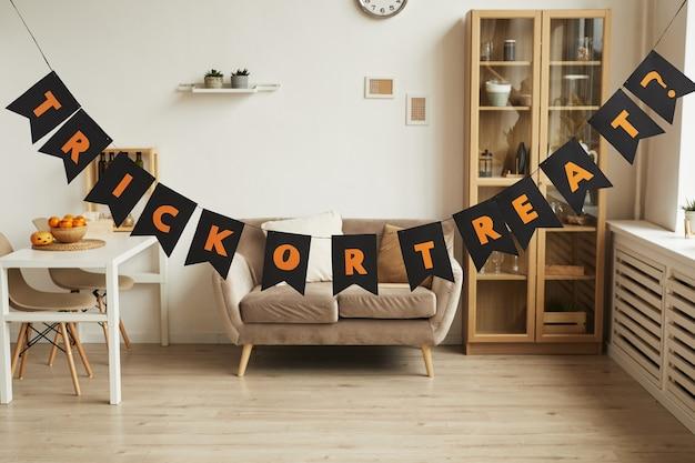 Poziome, bez ludzi ujęcie nowoczesnego wnętrza pokoju z girlandą z napisem trick or treat w nim przygotowanym na imprezę halloween