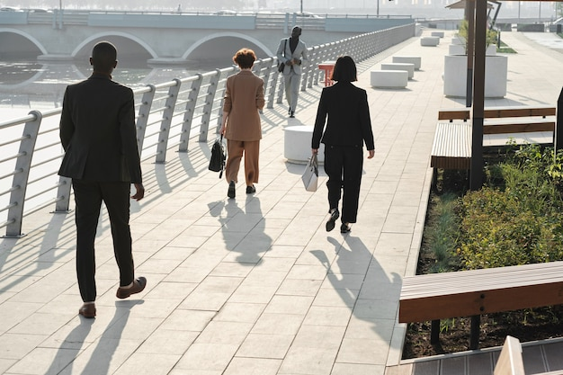 Poziome długie ujęcie nowoczesnych ludzi biznesu i pracowników biurowych idących do swoich miejsc pracy w słoneczny letni poranek
