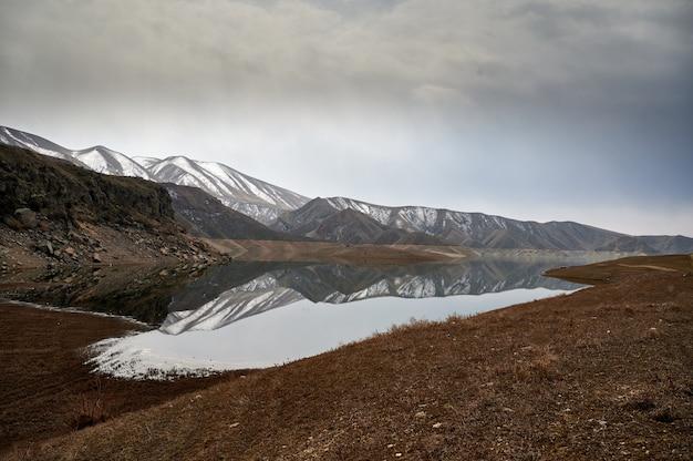 Poziome, malownicze ujęcie pasma górskiego odbitego w wodach zbiornika azat w armenii