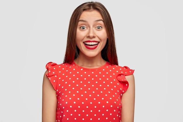 Poziome portret pięknej kobiety z czerwoną szminką, pozowanie na białej ścianie