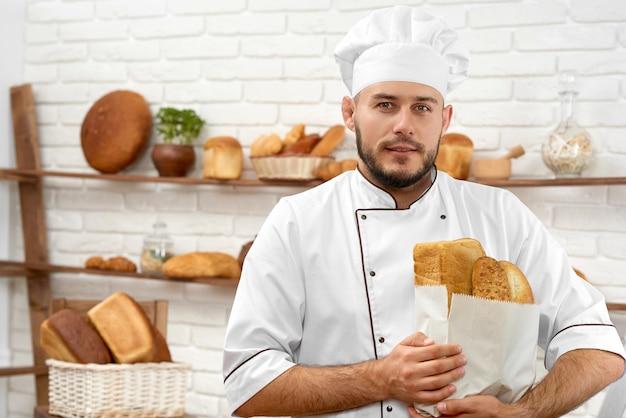 Poziome portret przystojny młody piekarz uśmiechnięty radośnie pozuje do swojej piekarni ze świeżo upieczonym chlebem w papierowej torbie copyspace konsumpcjonizm zakupy kupowanie usług gastronomicznych przyjazna praca.