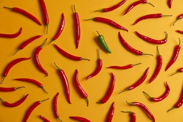 Poziome powyżej strzał selekcji gorącej czerwonej papryki chili i jeden zielony na białym tle na żółtym tle. świeże płonące warzywa do gotowania obiadu. koncepcja aromatyzowania i przypraw. bogate zbiory