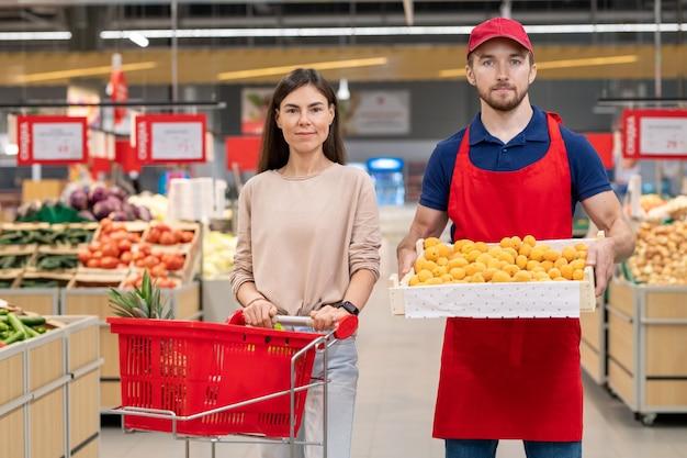 Poziome średnie ujęcie mężczyzny trzymającego pudełko owoców stojącego z młodą klientką w supermarkecie