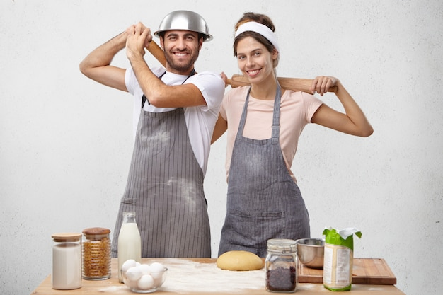 Poziome strzał dwóch kucharzy płci męskiej i żeńskiej w fartuchach posiadających wałki do ciasta