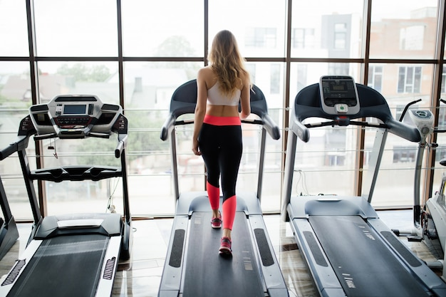 Poziome strzał kobiety joggingu na bieżni w klubie fitness. kobieta, poćwiczyć na siłowni, działa na bieżni.