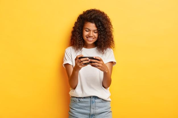 Poziome strzał millennial młoda kobieta z kręconymi włosami pozowanie z jej telefonem
