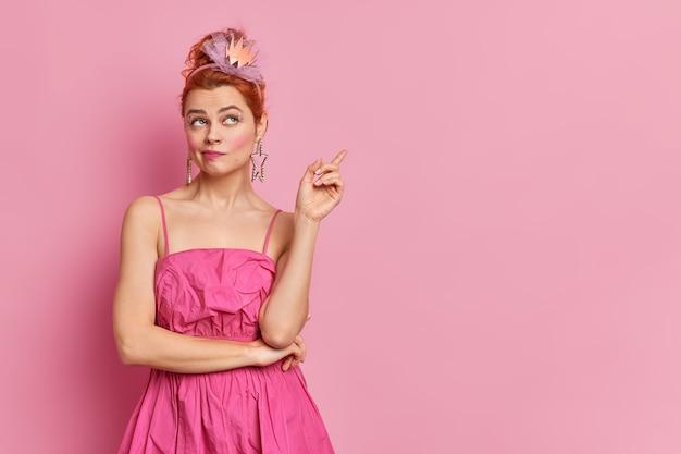 Poziome strzał rudowłosy modnej europejskiej kobiety ubranej w kostiumy przygotowuje się do imprezy w stylu lat dziewięćdziesiątych wskazuje na miejsce na kopię