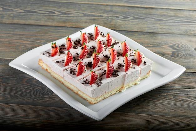 Poziome strzał świeżo upieczony pyszny sernik ozdobiony truskawkami na drewnianym stole ciasto gotowanie pieczenia deser śniadanie słodka koncepcja.