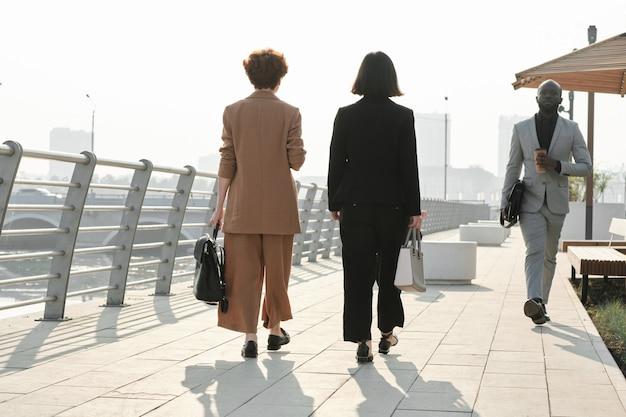 Poziome szerokie ujęcie nierozpoznawalnych kobiet i afroamerykanina w eleganckich formalnych ubraniach spacerujących wzdłuż brzegu rzeki w nowoczesnym mieście