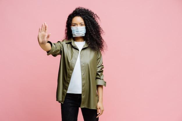 Poziome ujęcie afro amerykanki trzyma dłoń w kierunku kamery, robi gest zatrzymania, próbuje zapobiec koronawirusowi lub covid-19, nosi sterylną maskę ochronną, mówi światu pandemię