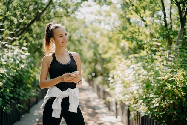 Poziome ujęcie aktywnej kobiety sportowej używa smartfona do sprawdzania wyników po joggingu ubrany w odzież sportową cieszy się ciepłym słonecznym dniem słucha muzyki przez słuchawki. pojęcie zdrowego stylu życia.