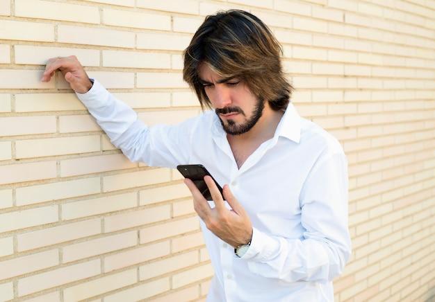 Poziome ujęcie atrakcyjnego młodego człowieka z długimi włosami, brodą, białą koszulą, opierającego się o ścianę wygląda na jego smartfona.