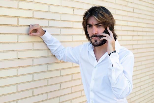 Poziome ujęcie atrakcyjnego młodego mężczyzny z długimi włosami, brodą, białą koszulą, opierającego się o ścianę mówi przez jego smartfona ze złością wygląda