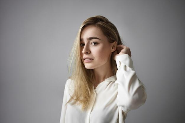 Poziome ujęcie atrakcyjnej blondynki w białej koszuli formalnej, dostosowując jej luźną fryzurę i patrząc na kamery z zamyślonym uśmiechem. ludzie, styl życia, ludzka mimika i moda