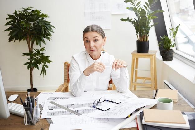 Poziome ujęcie atrakcyjnej kobiety w średnim wieku głównego architekta o zmęczonym wyglądzie podczas pracy w swoim biurze, otoczonej dokumentacją projektu budowlanego, narzędziami i ogólnym komputerem