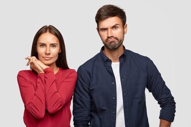 Poziome ujęcie atrakcyjnej młodej kobiety i jej chłopaka wygląda poważnie i myląco w cenach w sklepie, idźcie razem na zakupy, ubrani w zwykłe ubrania, odizolowani na białej ścianie.