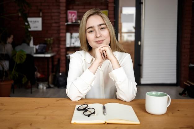 Poziome ujęcie atrakcyjnej, przyjaznej młodej kobiety w formalnej bluzce, ściskającej dłonie i radośnie uśmiechającej się do kamery, czującej się szczęśliwej i zainspirowanej podczas pracy w kawiarni, robienia notatek, picia kawy
