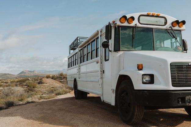 Poziome ujęcie białego autobusu z przodu na suchym polu w ciągu dnia
