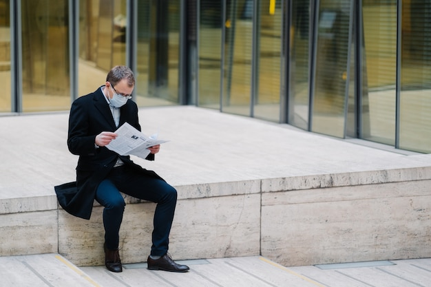 Poziome ujęcie biznesmena lub przedsiębiorcy przedstawia się na ulicy, czyta gazetę z uważnym spojrzeniem, nosi maskę medyczną w celu ochrony przed infekcją lub koronawirusem. samoobrona