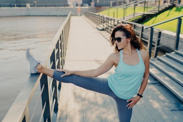 Poziome ujęcie brunetka kobieta nosi ubranie sportowe na co dzień rozciąga nogi na płocie