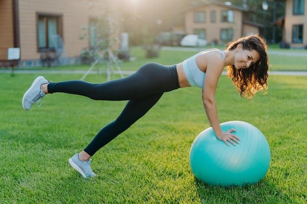 Poziome ujęcie brunetki pochyla się na piłce fitness, podnosi nogi i wykonuje ćwiczenia gimnastyczne, nosi topowe legginsy i trampki, pozuje na podwórku w pobliżu domu w dobry słoneczny dzień, oddycha świeżym powietrzem