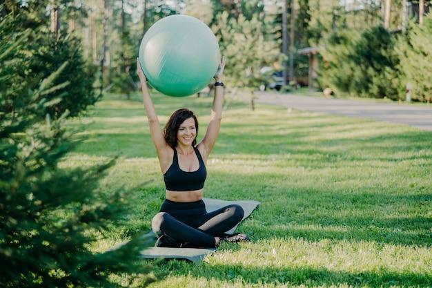 Poziome ujęcie brunetki sprawnej kobiety w aktywnym stroju siedzi w pozycji lotosu na karemacie trzyma piłkę fitness nad głową ma ćwiczenia gimnastyczne na świeżym powietrzu w słoneczny dzień, uśmiecha się przyjemnie, cieszy się naturą