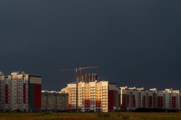 Poziome ujęcie budynków na budowie pod zachmurzonym niebem o zachodzie słońca
