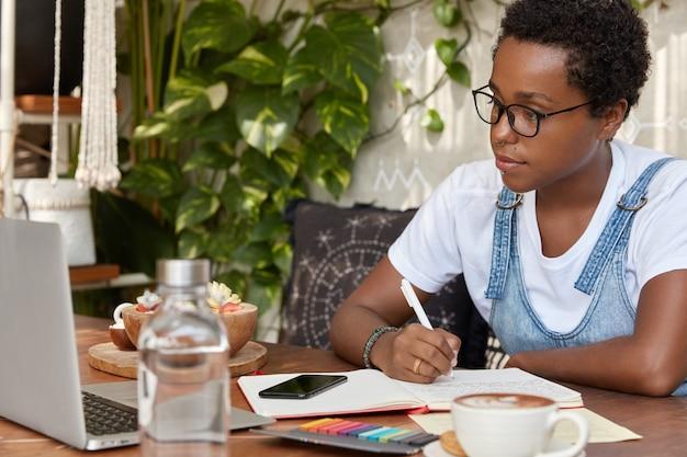 Poziome ujęcie całkiem ciemnoskórego pracownika siedzi przy laptopie i uczy się informacji z wideo