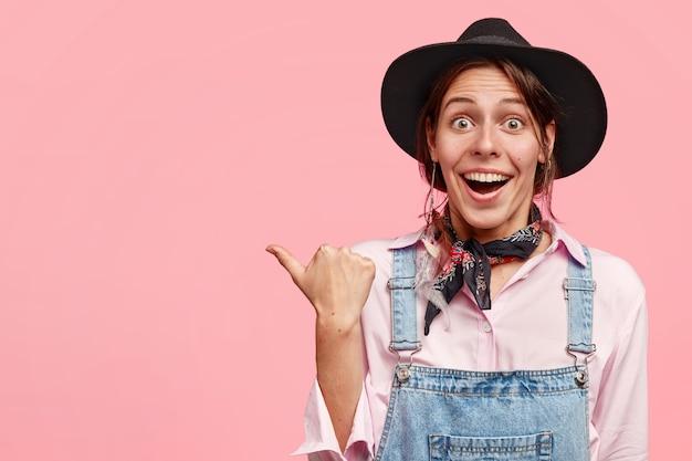 Poziome ujęcie całkiem kobiece ogrodnik z pozytywnym wyrazem, wskazuje na bok kciukiem, ubrana w dorywczo kombinezon i czarny kapelusz