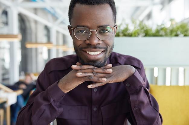 Poziome ujęcie ciemnoskórego przedsiębiorcy odnoszącego sukcesy w okularach i fioletowej koszuli, radośnie patrzy w kamerę, pokazuje nawet białe zęby