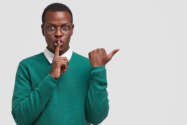 Poziome ujęcie ciemnoskórego tajemniczego mężczyzny wykonuje gest ciszy, wskazuje na bok, demonstruje znak uciszenia