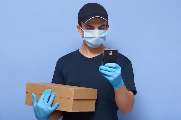 Poziome ujęcie człowieka dostawy ze swoim smartfonem w rękach, znajdującego adres dostawy lub połączenia z klientem, noszącego odzież ochronną, aby zapobiec rozprzestrzenianiu się wirusa korony.